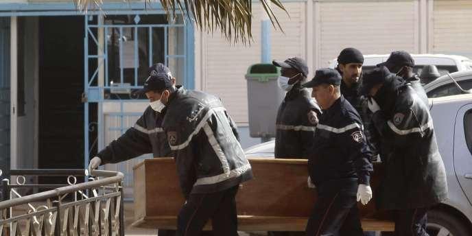 Des secouristes portent un cercueil dans le site gazier d'In Amenas, lundi 21 janvier 2013.
