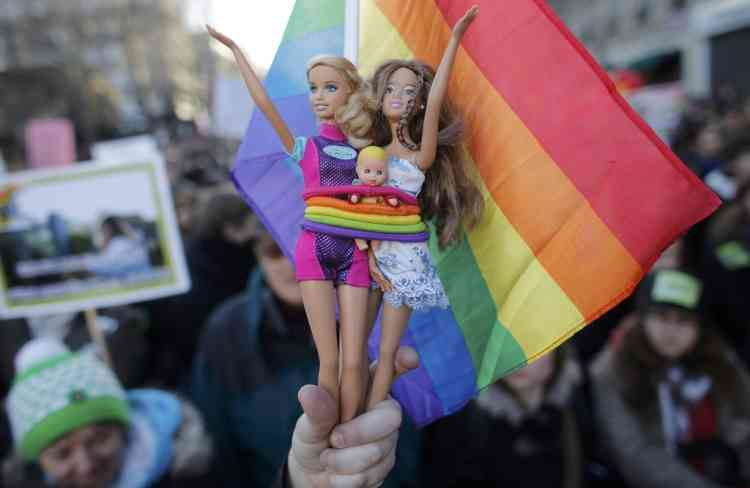 A demonstrator holds Barbie dolls as people march through the streets of Paris in support of the French government's draft law to legalise marriage and adoption for same-sex couples, January 27, 2013.     REUTERS/Christian Hartmann (FRANCE  - Tags: POLITICS RELIGION)