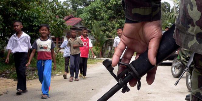 Des enfants musulmans passent devant un soldat thaïlandais chargé d'assurer la protection d'un village de la province de Narathiwat, après que 35 enseignants y ont été pris en otage, le 9 février 2006.