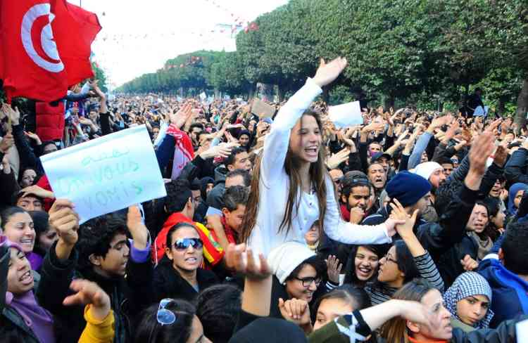 Protesters gather on Tunis 'main avenue after a Tunisian opposition leader critical of the Islamist-led government was gunned down as he left home Wednesday, Feb.6, 2013.  Chokri Belaid was gunned down as he left home in the first assassination in post-revolutionary Tunisia. The killing of Belaid, a 47-year-old lawyer, heightens tensions in the North African nation whose path from dictatorship to democracy has been seen as a model for the Arab world so far. Poster at left reads: Man vomited on you. (AP Photo/Hassene Dridi)