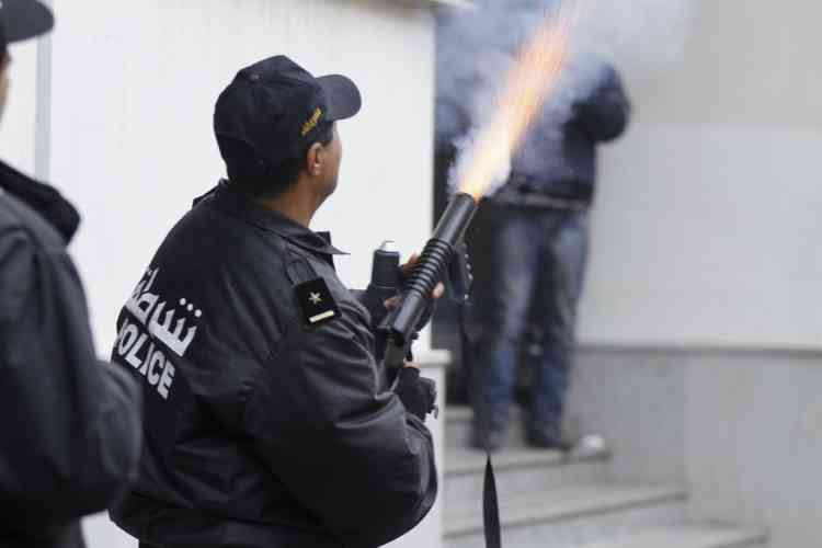 A police officer fires teargas to break up a protest during a demonstration in Tunis February 6, 2013. Tunisian police fired teargas to disperse protesters demonstrating in the capital outside the Interior Ministry against the killing of a prominent secular opposition politician on Wednesday, witnesses said. REUTERS/ Anis Mili (TUNISIA - Tags: CIVIL UNREST POLITICS)