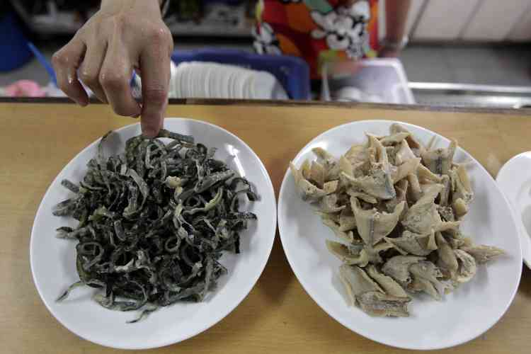 An employee prepares dishes of fried cobra skin (L) and cobra meat at a snake farm ahead of the Spring Festival in Tainan, southern Taiwan, February 5, 2013. A dish of fried cobra skin is priced around USD$7 (NTD$200). The Lunar New Year, also known as the Spring Festival, begins on February 10 and marks the start of the Year of the Snake, according to the Chinese zodiac. Picture taken February 5, 2013. REUTERS/Pichi Chuang (TAIWAN - Tags: SOCIETY ANIMALS)