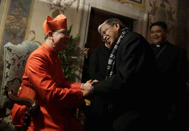 Newly installed Cardinal Luis Antonio Tagle of the Philippines (L) receives guests in the Regia Hall at the Vatican November 24, 2012. Pope Benedict XVI installed six new Roman Catholic cardinals from around the world on Saturday. REUTERS/Tony Gentile (VATICAN - Tags: RELIGION) - RTR3ATYI