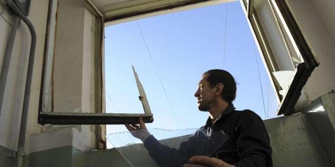 Un homme répare une vitre brisée par une météorite, à Tcheliabinsk, le 15 février.