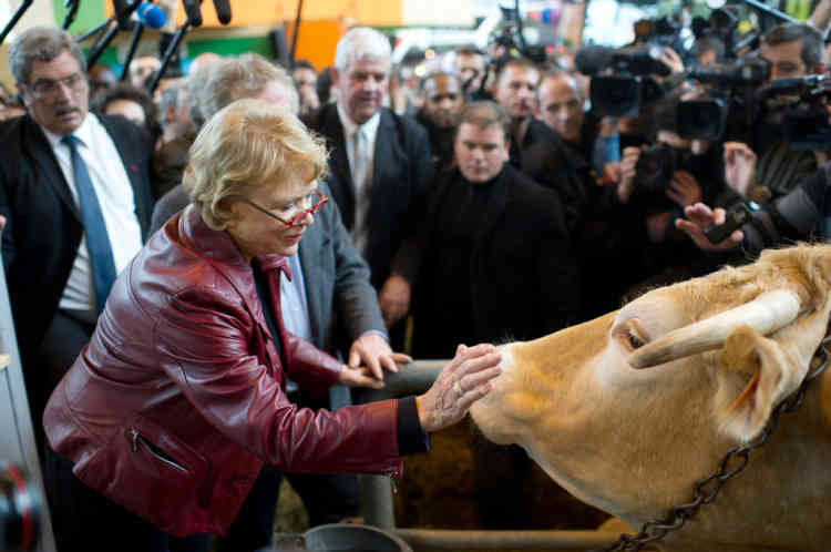 """French Green Party """"Europe Ecologie Les Verts"""" (EELV) candidate for the 2012 French presidential election, Eva Joly (C) pets a cow as she visits the Paris International Agricultural fair at the Porte de Versailles exhibition center, on March 1, 2012 in Paris. AFP PHOTO / MARTIN BUREAU"""