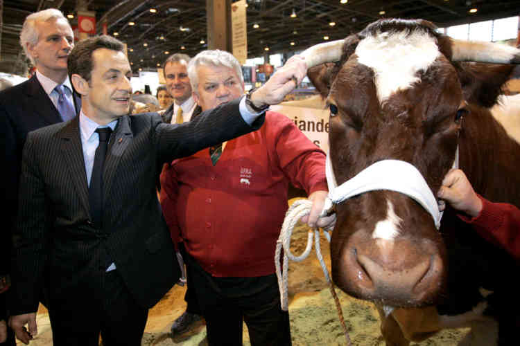 French President Nicolas Sarkozy (2dL) touches a Maine Anjou breed of cattle as he visits The International Agricultural Fair with Agriculture minister Michel Barnier (L) on February 23, 2008 in Paris. The fair is opened to the public from February 23th to March 2nd 2008. Nicolas Sarkozy said today he wants to see French gastronomy classed as a world heritage by UNESCO, at the opening of the country's huge annual agriculture show. AFP PHOTO POOL THIBAULT CAMUS