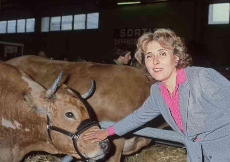 Edith Cresson, ministre de l'Agriculture, caresse le museau d'une vache parthenaise (Deux-Sèvres), en inaugurant le 20ème salon de l'Agriculture, le 7 Mars 1983, à la Porte de Versailles à Paris.