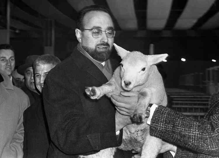Edgar Pisani, ministre français de l'Agriculture, tient un agneau qu'un exposant lui présente lors de sa visite au salon de l'agriculture le 06 mars 1965 à paris. M. Pisani a inauguré officiellement le salon de l'agriculture qui a ouvert ses portes la veille et qui se poursuivra jusqu'au 14 mars 1965. AFP PHOTO