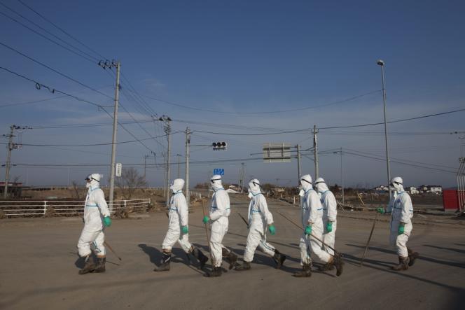 Des policiers japonais à l'intérieur de la zone interdite de 20 km autour de la centrale de Fukushima.