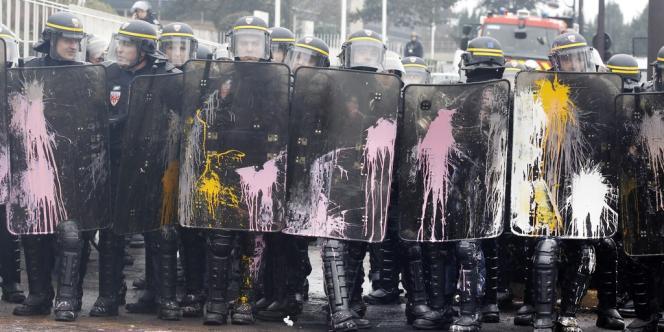 Des CRS aspergés de peinture devant le siège de Goodyear.