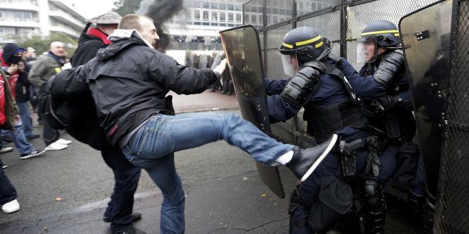 Un manifestant se bat avec un CRS devant le siège de Goodyear, jeudi 7 mars.