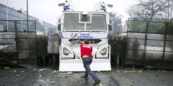 Un manifestant devant un camion anti-émeute.