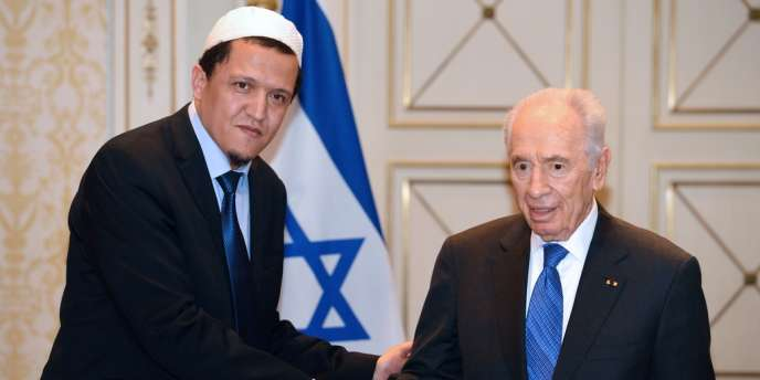 Le président israélien, Shimon Pérès, et l'imam Hassen Choulgami se serrent la main le 10 mars 2013.