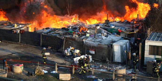 Des pompiers s'affairent pour éteindre un incendie déclaré dans un camp de Roms, le 7 février 2011 à Bobigny.