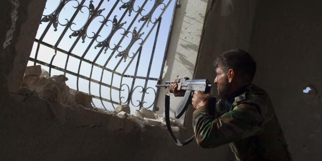 Un combattant rebelle pointe son arme sur les hommes de l'armée syrienne à l'aéroport militaire de Menagh, près d'Alep, dans le nord de la Syrie, le 13 mars.