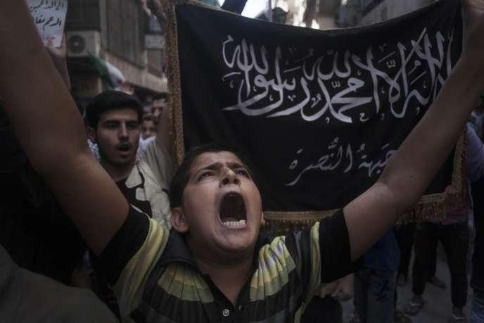 Un enfant syrien chante des slogans contre le régime, devant un drapeau du Front Al-Nousra, dans un quartier d'Alep, le 21 septembre 2012.