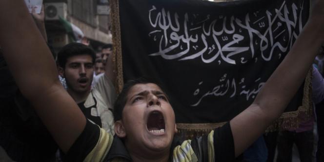 Une jeune manifestant anti-Assad, avec derrière lui le drapeau du Front Al-Nousra, près d'Alep, en septembre 2012.