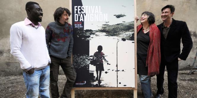 Dieudonné Niangouna, Stanislas Nordey (à gauche), artistes associés, avec Hortense Archambault et Vincent Baudriller (à droite), directeurs, autour de l'affiche du 67e Festival d'Avignon, le 18 mars 2013.