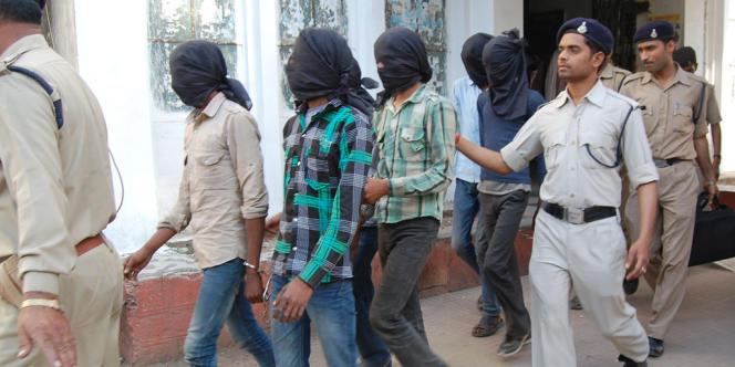 Des policiers escortent 5 hommes arrêtés pour le viol collectif d'une touriste suisse, le 18 mars.