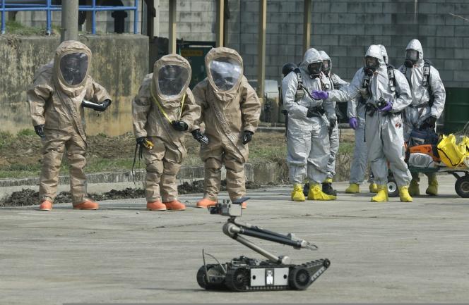 Des militaires américains présentent leurs combinaisons de protection contre les menaces nucléaires, bactériologiques et chimiques, à Camp Stanley à Uijongbu, au nord de Séoul, le 4 avril 2013.