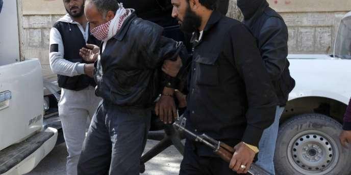 Des membres du groupe djihadiste Al-Nosra détiennent un prisonnier dans la province de Rakka, dans l'est de la Syrie, le 14 mars 2013.