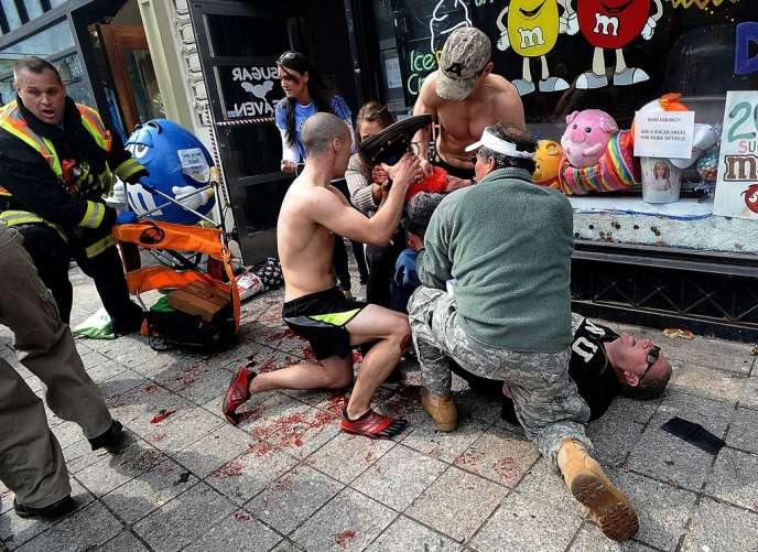 Des personnes tentent de donner les premiers soins à un homme blessé par la double explosion qui a eu lieu pendant le marathon de Boston.