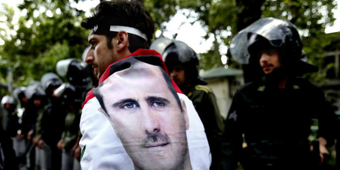 Un Syrien portant un drapeau à l'effigie de Bachar Al-Assad.