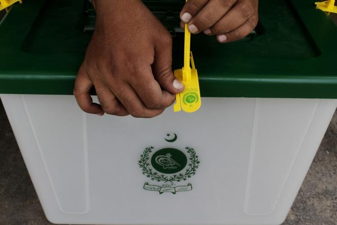 Un employé de la commission électorale pose un sceau sur une urne, le 6 mai à Karachi.