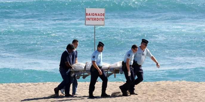 Des gendarmes transportent le corps du surfeur français tué par une attaque de requin mercredi 8 mai sur la plage de Saint-Gilles à l'île de La Réunion.