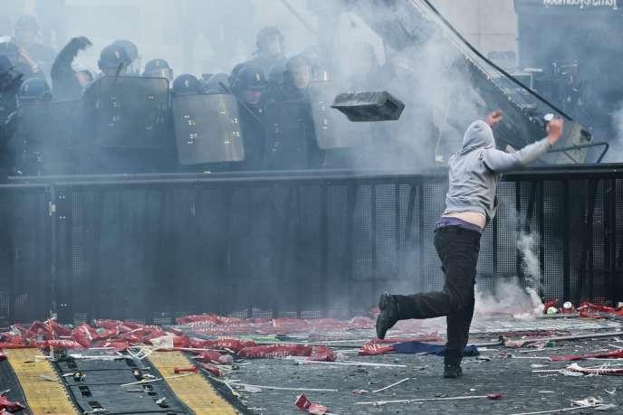 Un supporter du PSG lance un parpaing sur les CRS, place du Trocadéro à Paris, le 13 mai. Treize personnes ont été jugée en comparution immédiate deux jours après les scènes d'émeutes.