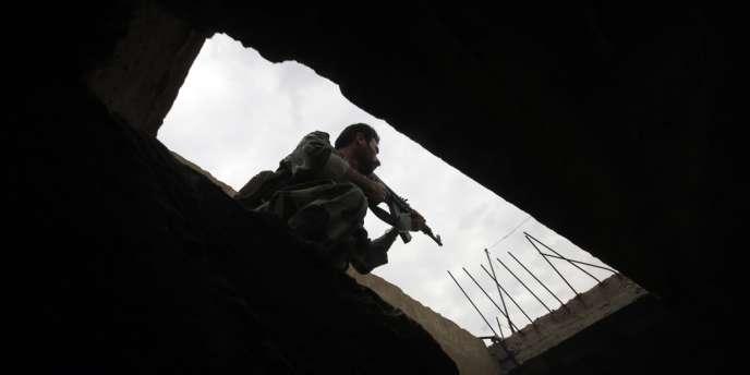Un soldat de l'armée syrienne inspecte une maison à Qusayr, dans la province de Homs, lundi.
