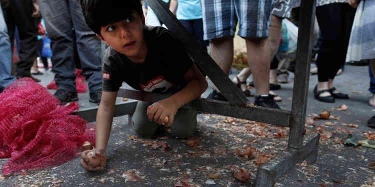 Un garçon récupère des oignons distribués gratuitement par des agriculteurs, au cours d'une manifestation à Athènes, le 15 mai.