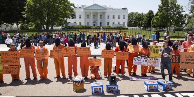 Des militants vêtus de combinaisons orange et de cagoules noires s'alignaient devant les grilles de la Maison Blanche pour délivrer le même message :