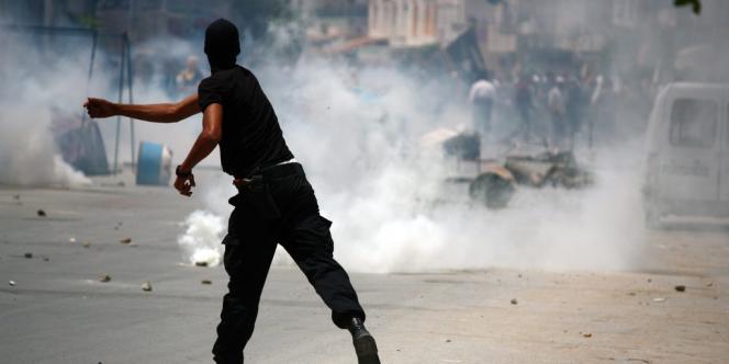 Un officier de police tunisien dans les affrontements qui ont opposé les forces de sécurité et les militants de l'organisation salafiste djihadiste Ansar al-charia, à Ettadhamen, à Tunis, le 19 mai 2013.