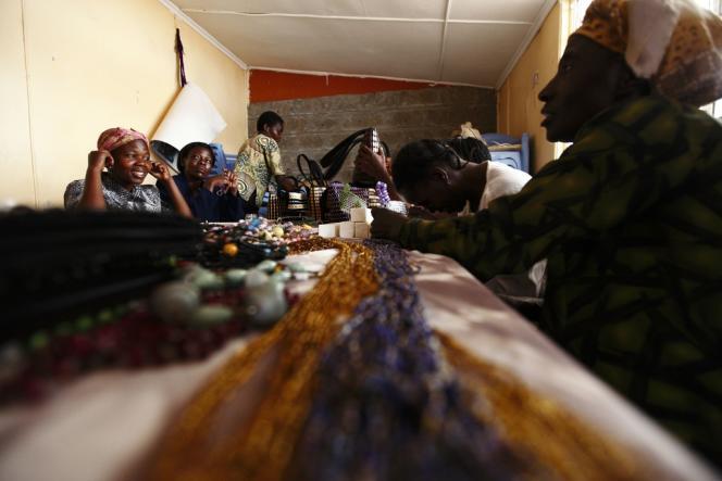 Des femmes séropositives travaillent dans un atelier de confection de colliers, dans un quartier de Nairobi, au Kenya.