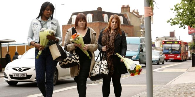 Mercredi 23 mais, des femmes déposent des fleurs là où un soldat britannique a été assassiné, la veille, par deux jeunes hommes dans le sud-est de Londres.