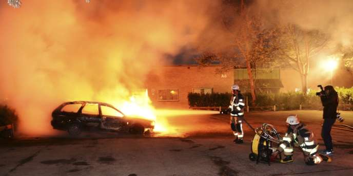 Des pompiers éteignent un véhicule incendié, le 21 mai, à Kista, dans la banlieue de Stockholm.