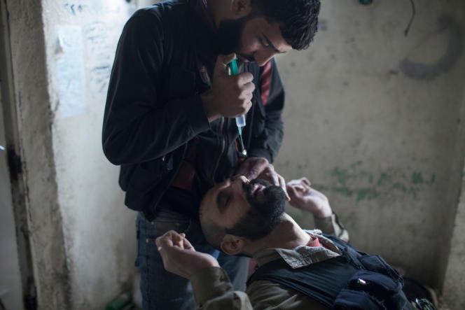 Un combattant de l'ASL reçoit des doses d'atropine dans les yeux pour prévenir les effets des gaz toxiques, à Jobar, près de Damas.