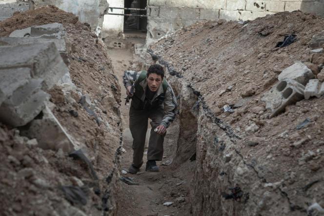 Un combattant de la brigade se faufile, le 3 avril 2013, dans des tranchées entre les maisons situées en face de la place stratégique des Abbasides, l'un des verrous de Damas.