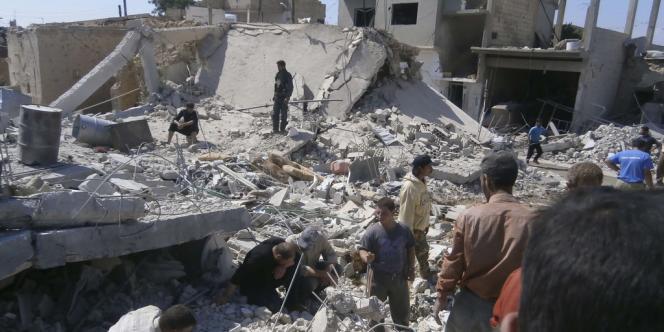 Des civils cherchent des survivants dans des immeubles détruits par un bombardement de l'armée syrienne, mardi 21 mai, à Qoussair.