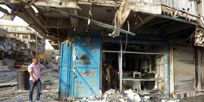 Des Irakiens inspectent les dommages après une attaque à la voiture piégée dans une rue commerçante de Bagdad, le 27 mai 2013.