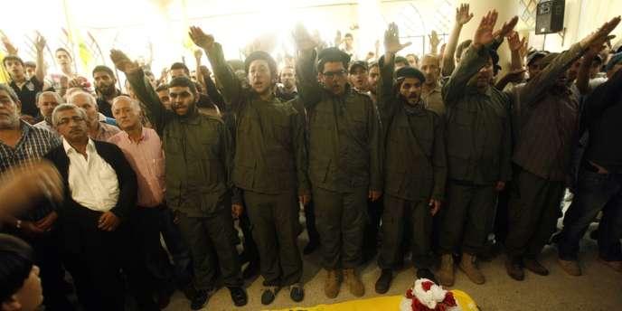 Des militants du Hezbollah saluent la dépouille de l'un de leurs camarades tué en Syrie, en mai 2013.