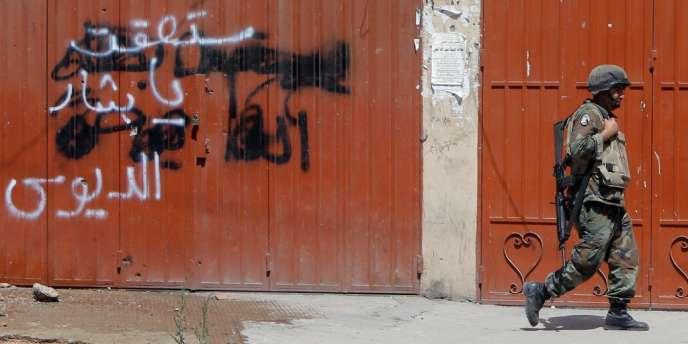 Un militaire libanais devant un graffiti anti-Assad.