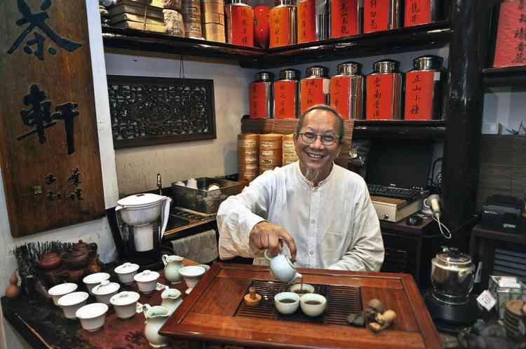 """Savourer le thé de Maître Ip""""La flambée des loyers a contraint à déménager entre autres les magasins qui donnaient du cachet à Central. Connu pour abriter le temple Man Mo dédié, entre autres, au dieu de la littérature, Sheung Wan a accueilli à bras ouverts créateurs, antiquaires et le négoce traditionnel,  des épices à la médecine chinoise. M. Ip Wing Chi règne  sur une maison de thé. Ce spécialiste renommé se plaît  à partager son savoir. Il faut prendre le temps de s'asseoir pour goûter avant d'acheter. L'amateur éclairé sera invité  à visiter l'arrière-boutique."""" Photo: Eric Rechsteiner/Panos pictures pour M Le magazine du Monde"""