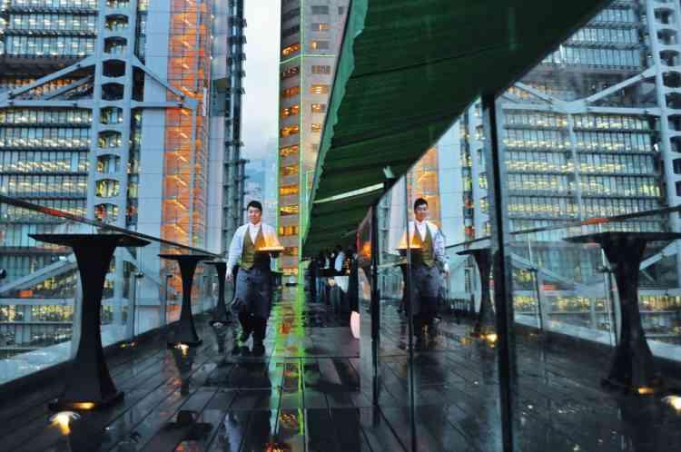 """Prendre de la hauteur à Sevva's""""Conformément à la tradition anglo-saxonne, le Happy Hour est de rigueur pour décompresser après le travail. Sevva's accueille le monde des affaires en costume-cravate. Sur la terrasse, la vue est grandiose. Siroter confortablement un """"Kama-Sutra"""", face à la tour Hongkong & Shanghai Bank vaut le déplacement. La gargote de Tung Po aussi (photo), quoique dans un genre différent et à vingt minutes en taxi. Ici, le patron accueille sa clientèle, droit dans ses bottes de caoutchouc. Avant de s'asseoir sur  les tabourets plastifiés, on sélectionne son dîner dans l'aquarium. Les mérous sont cuits à la perfection."""" Photo: Eric Rechsteiner/Panos pictures pour M Le magazine du Monde"""