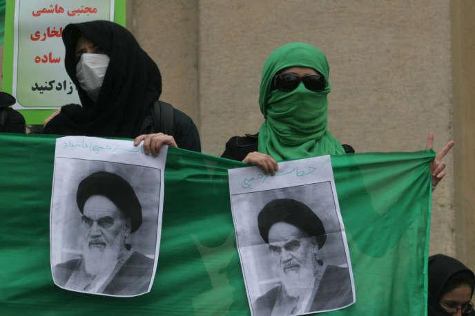 Des opposants brandissent des images à l'effigie de l'Ayatollah Khomeini, quelques mois après le printemps vert, à Téhéran, en décembre 2009.