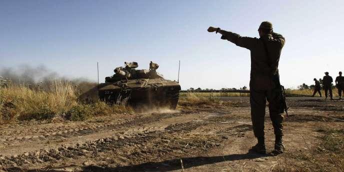 Un soldat israélien dirige les manoeuvres d'un tank sur le plateau du Golan, en juin 2013.