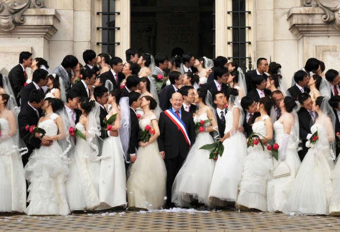Trente et un couples chinois originaires de la ville de Tianjin et Jean Germain (au centre) devant la mairie de Tours, en mai 2009.
