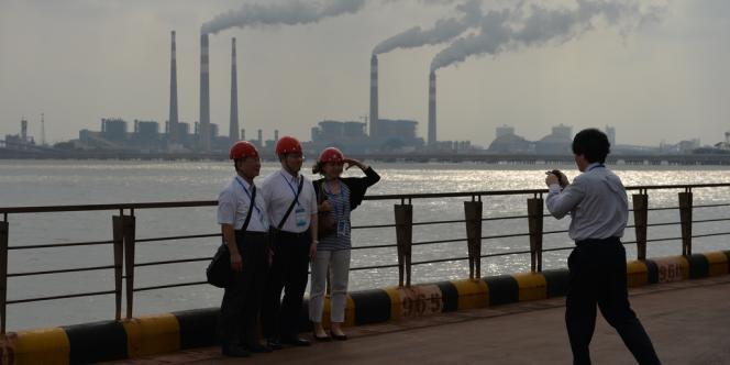 Des visiteurs devant une aciérie, à Shanghaï.