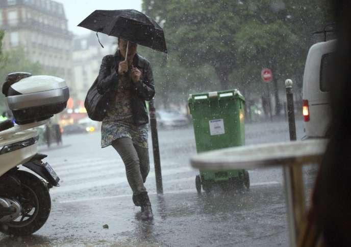 Une passante sous les orages à Paris, le 17 juin 2013.